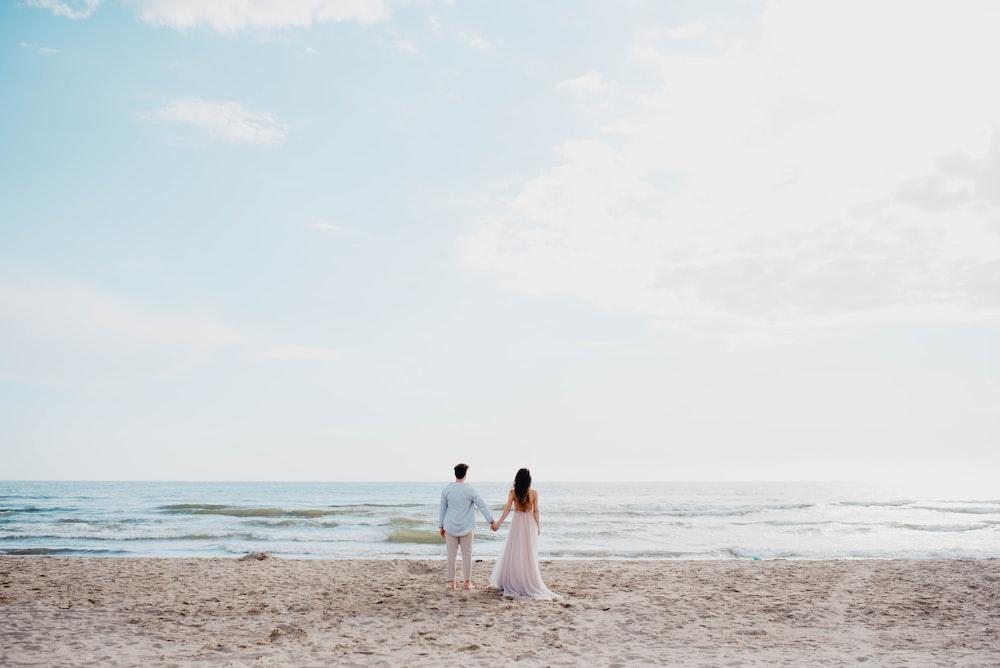 2 women in white dress walking on beach during daytime