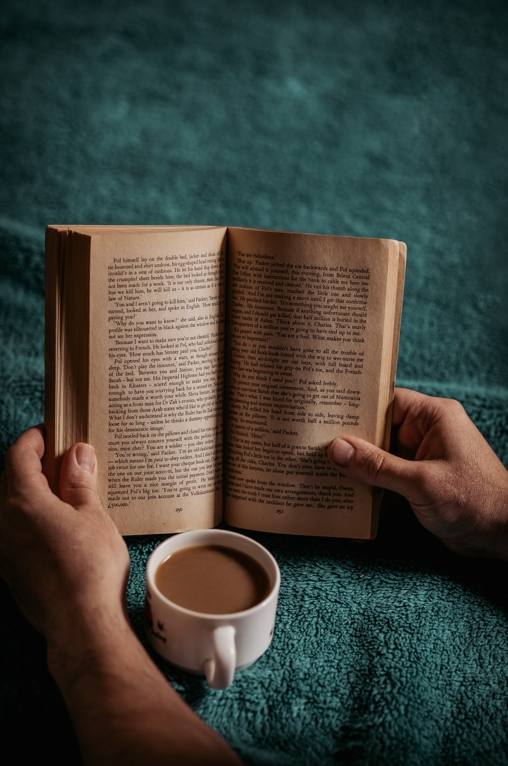 person reading book on green textile