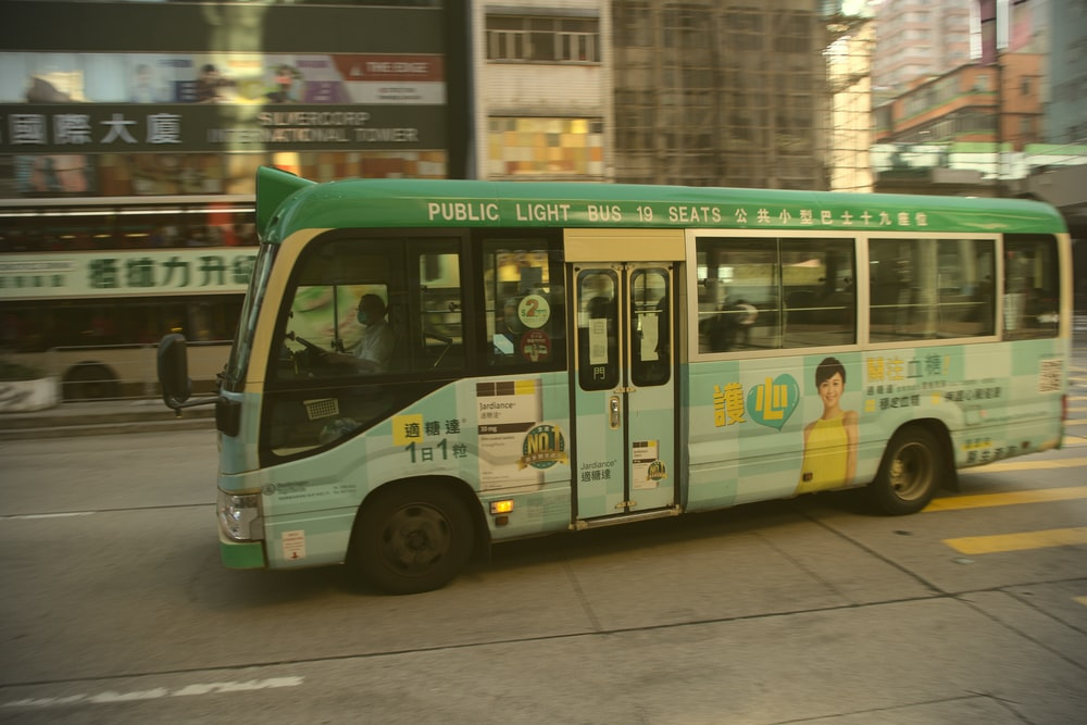 green and white bus on road during daytime