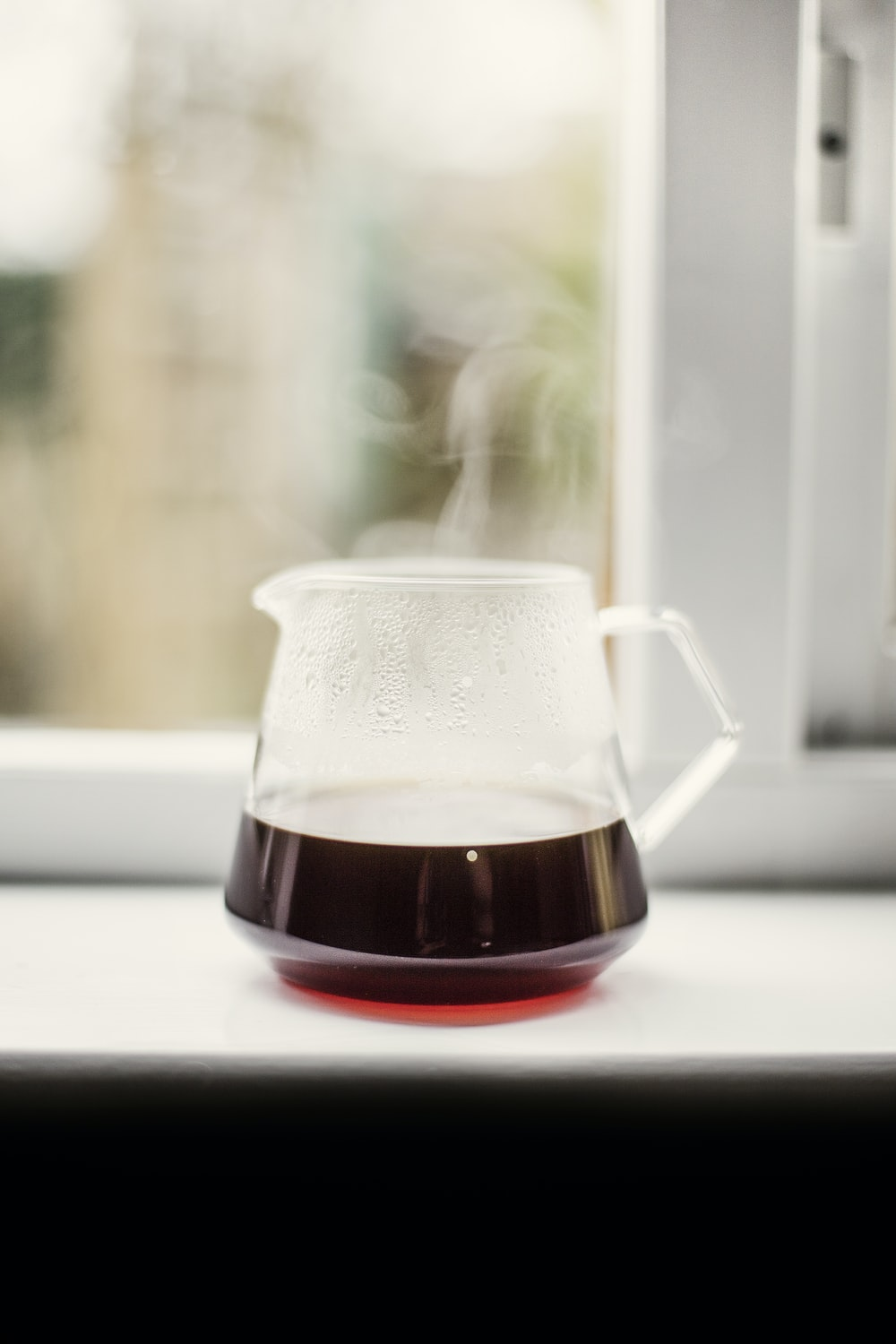 clear glass pitcher with brown liquid