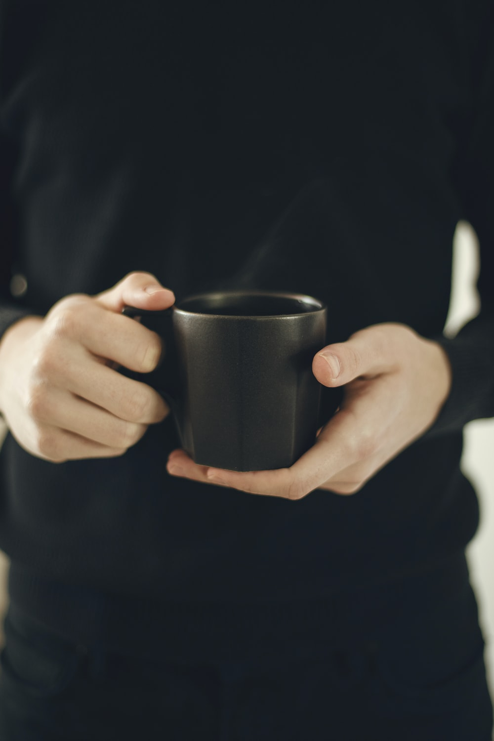 person holding black ceramic mug