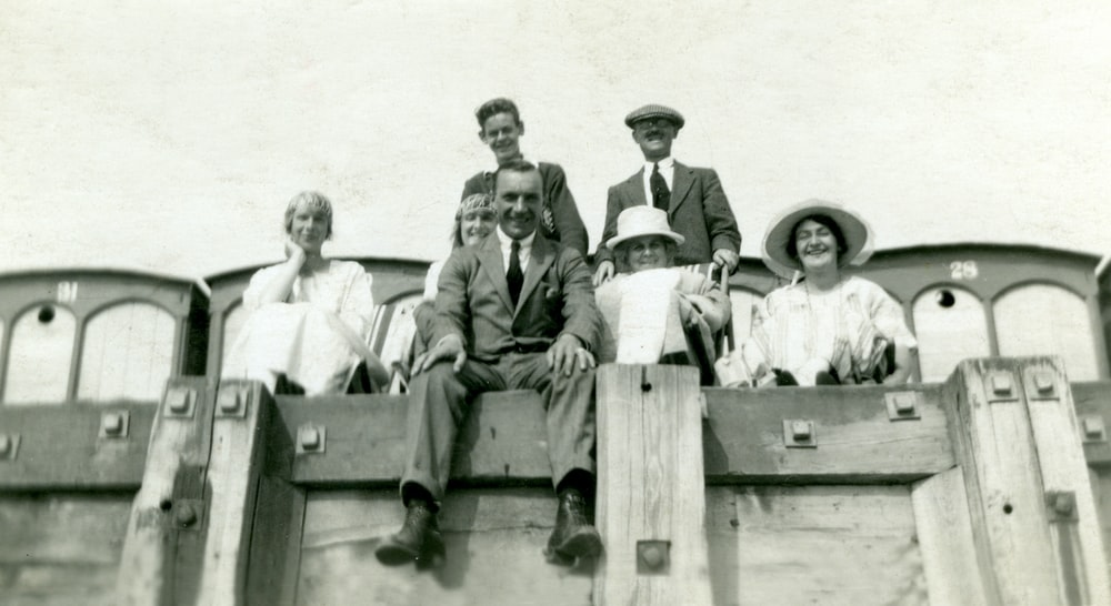 grayscale photo of 3 men and 2 women sitting on wooden bench