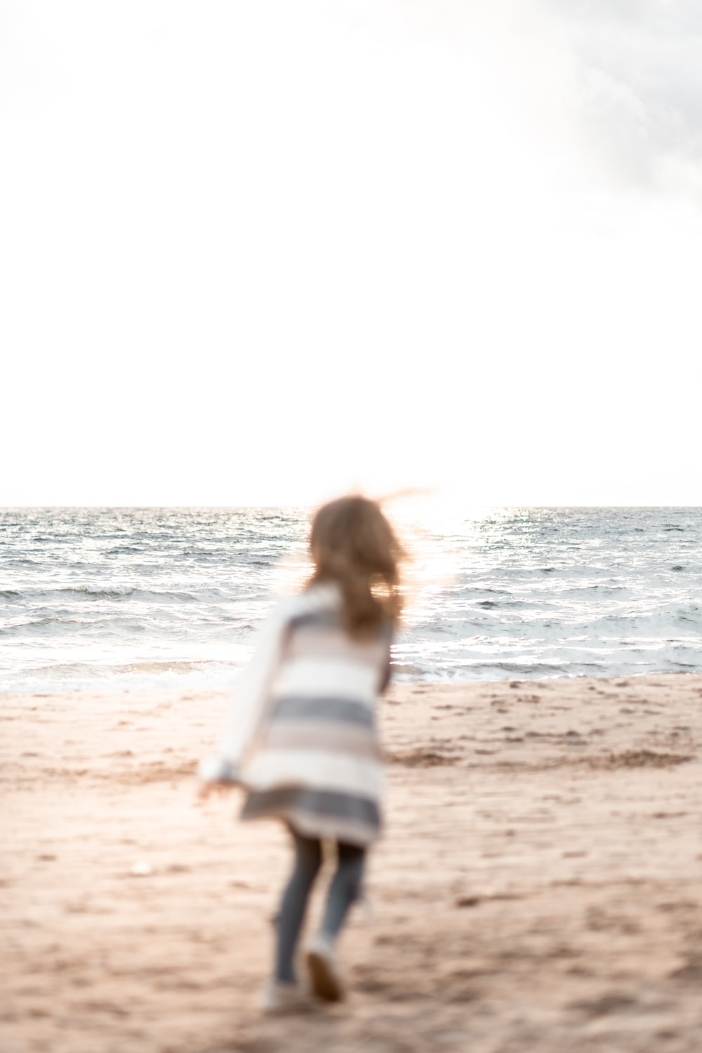 woman in white and blue stripe long sleeve shirt standing on beach during daytime