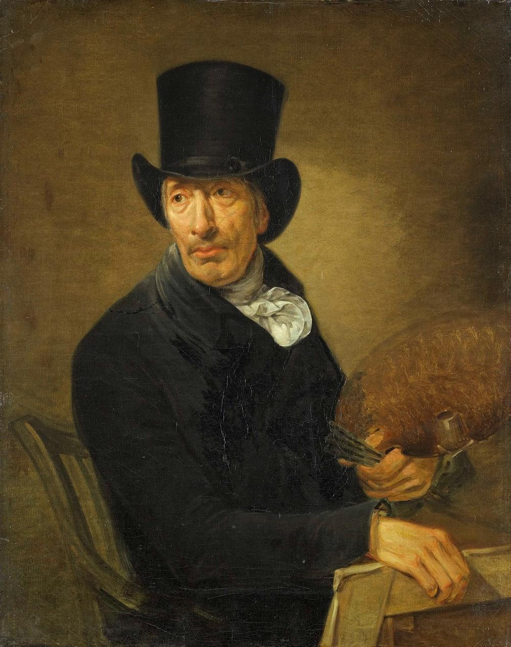 man in black cowboy hat holding brown animal