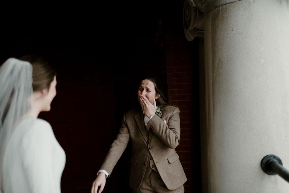 man in brown coat standing beside woman in white dress