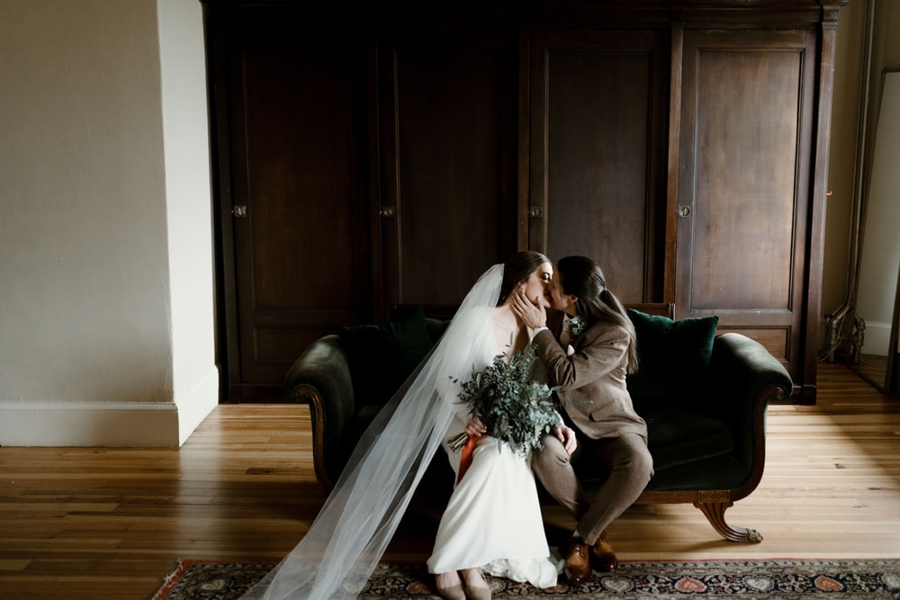woman in white wedding gown sitting on brown wooden floor