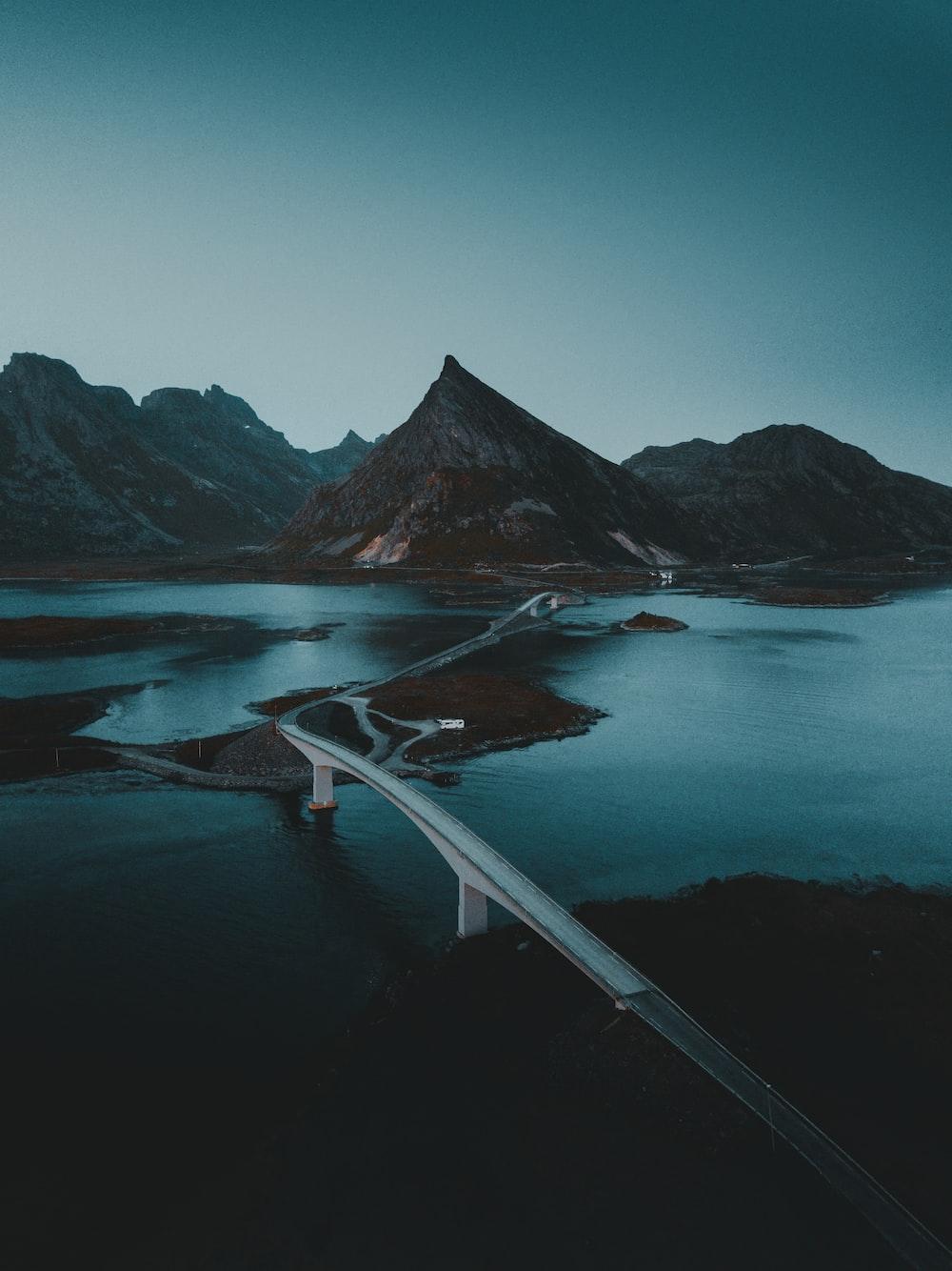 white bridge across lake and mountain during daytime