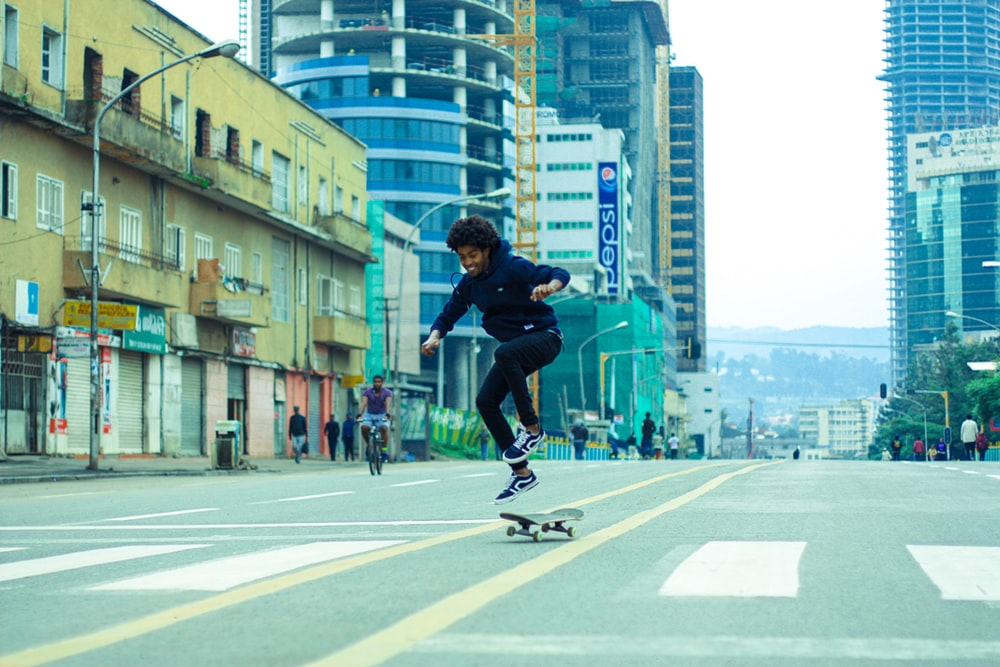man in black shirt and black pants doing skateboard stunts on gray concrete road during daytime