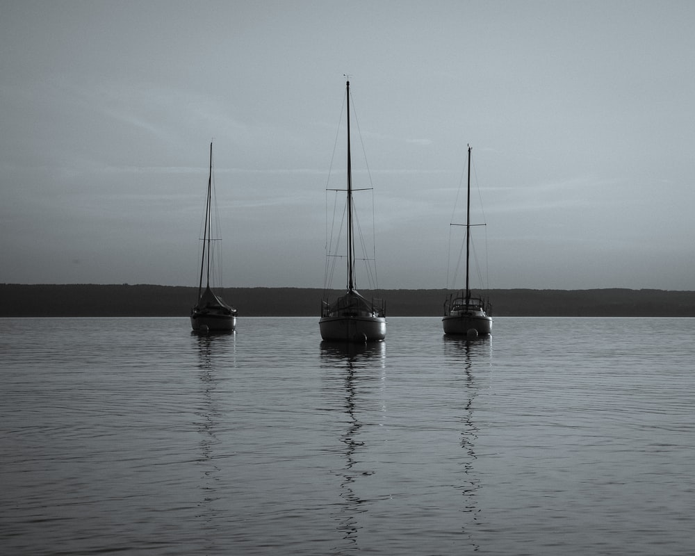 two sail boats on sea under gray sky