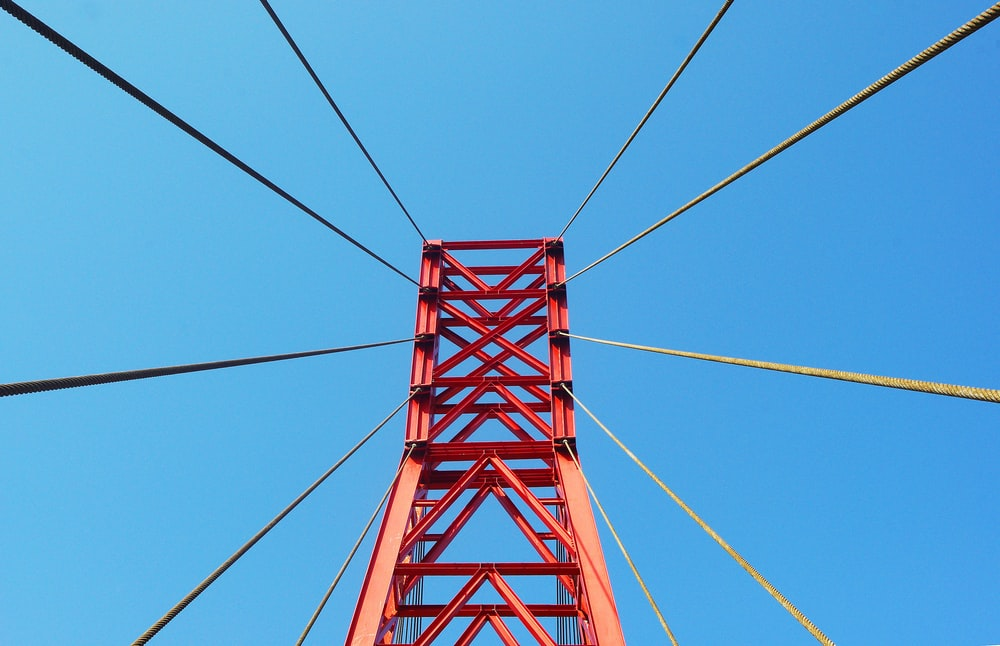 red metal bridge under blue sky during daytime