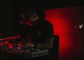 man in black crew neck t-shirt wearing black cap using black laptop computer
