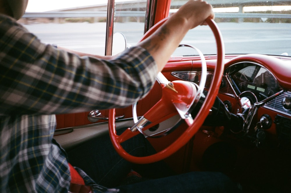 person in black and white plaid long sleeve shirt driving car