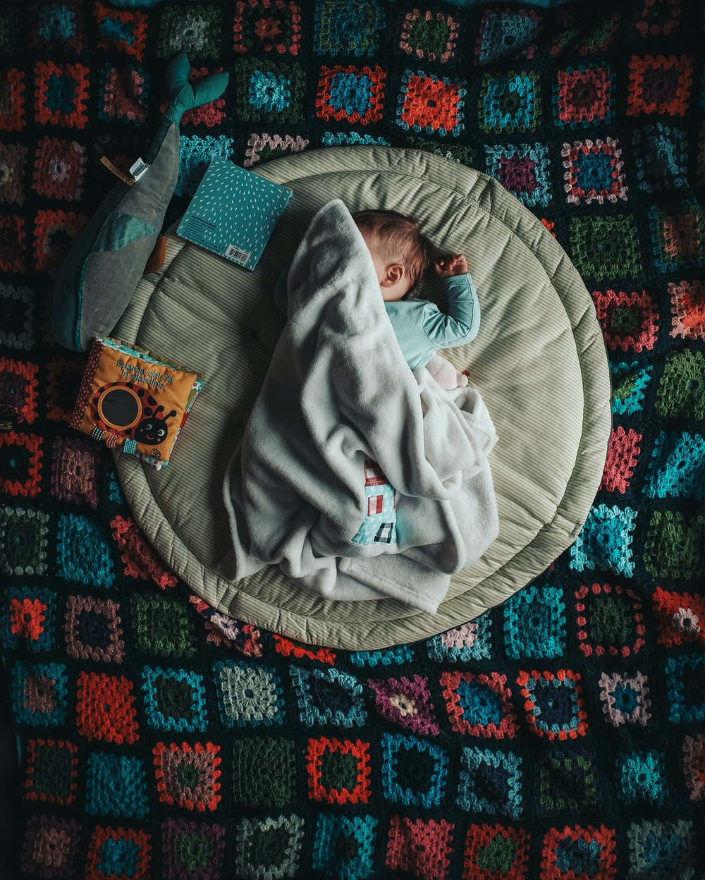 baby in white onesie lying on white and green rock and play sleeper