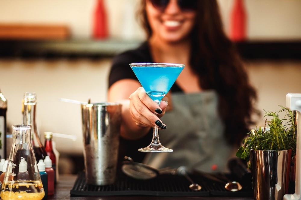 woman in black framed eyeglasses holding cocktail glass