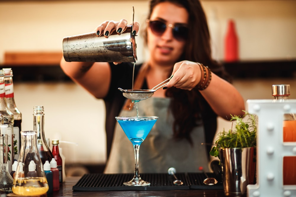woman pouring water on cocktail glass
