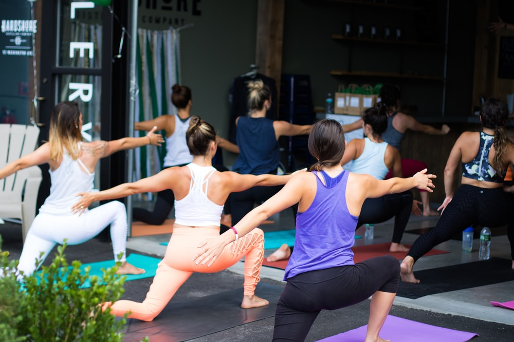 woman in white tank top and pink leggings doing yoga circlemagazine-metabolism