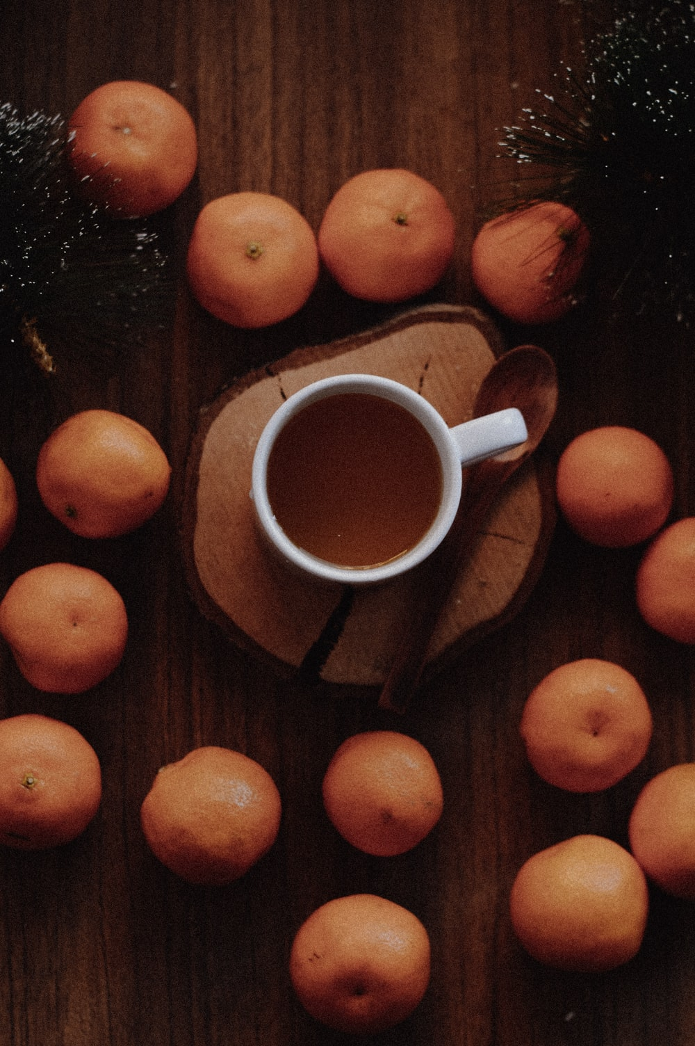 white ceramic mug on orange fruits