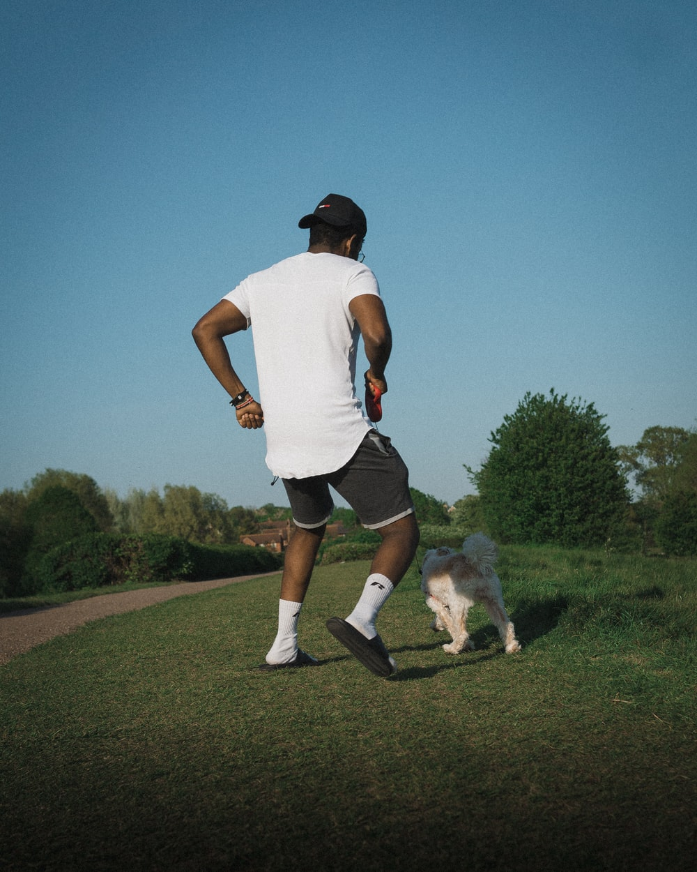 man in white t-shirt and black shorts running on green grass field during daytime