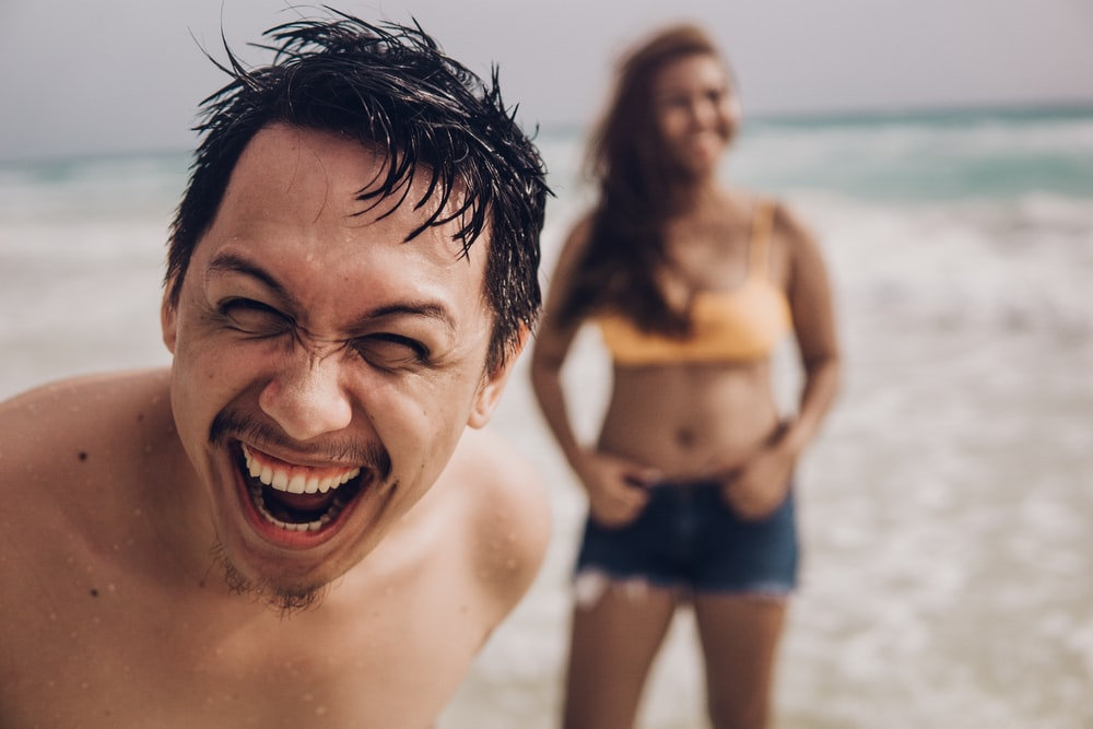 smiling man in blue shorts on beach during daytime