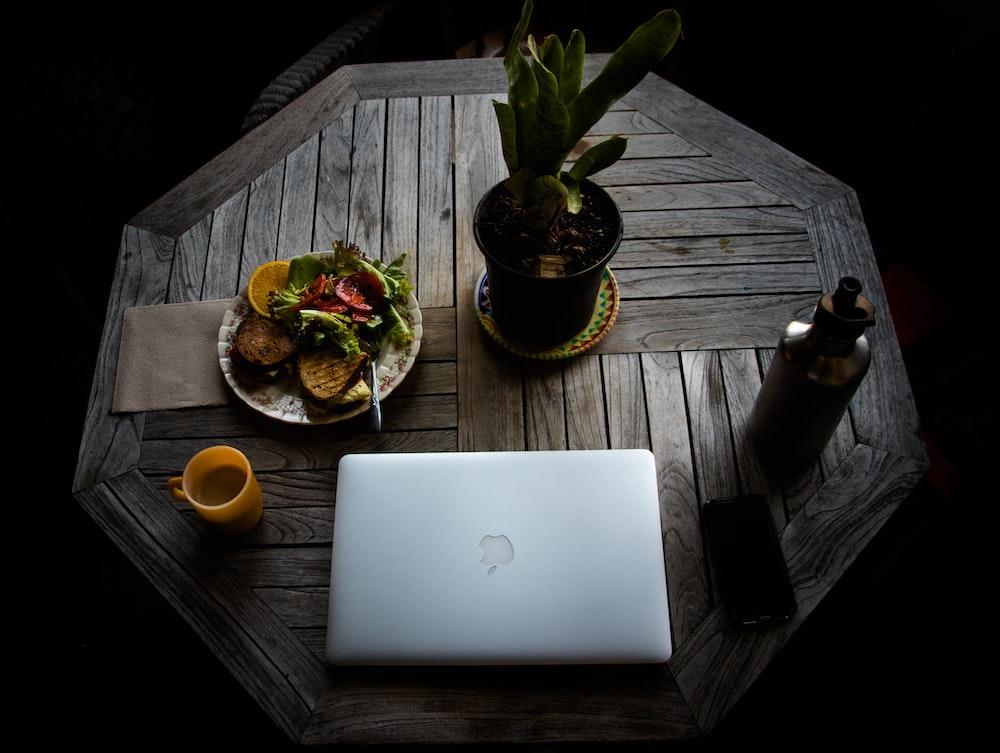 silver macbook beside orange fruit on brown wooden table