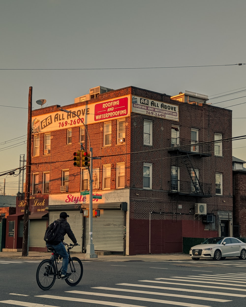 man in black jacket riding bicycle near brown concrete building during daytime