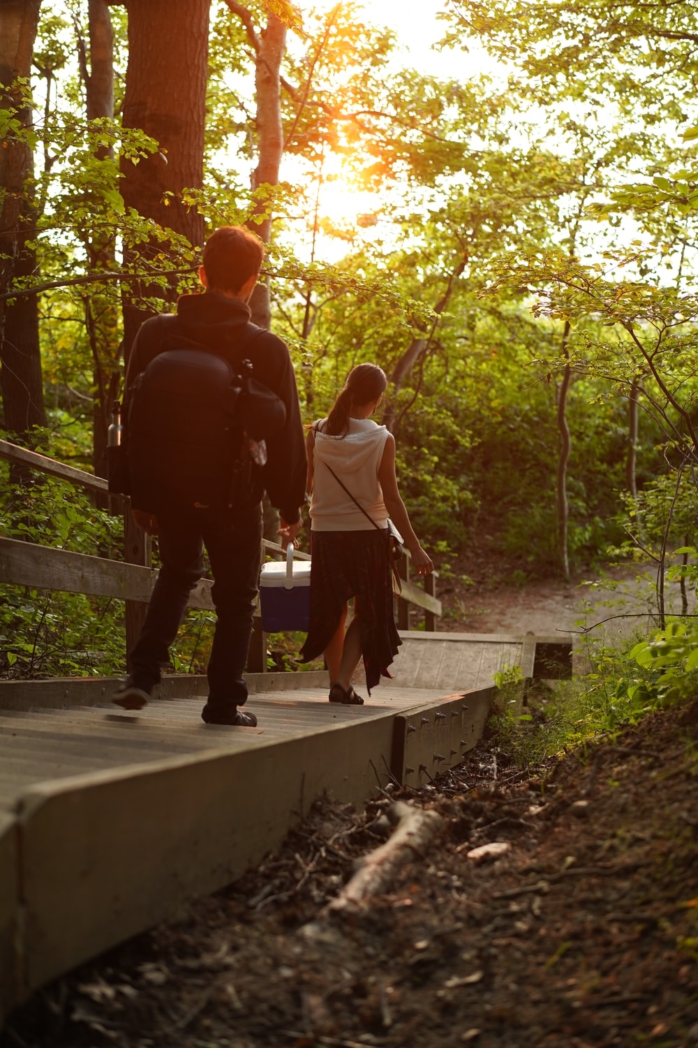 man and woman walking on pathway between trees during daytime