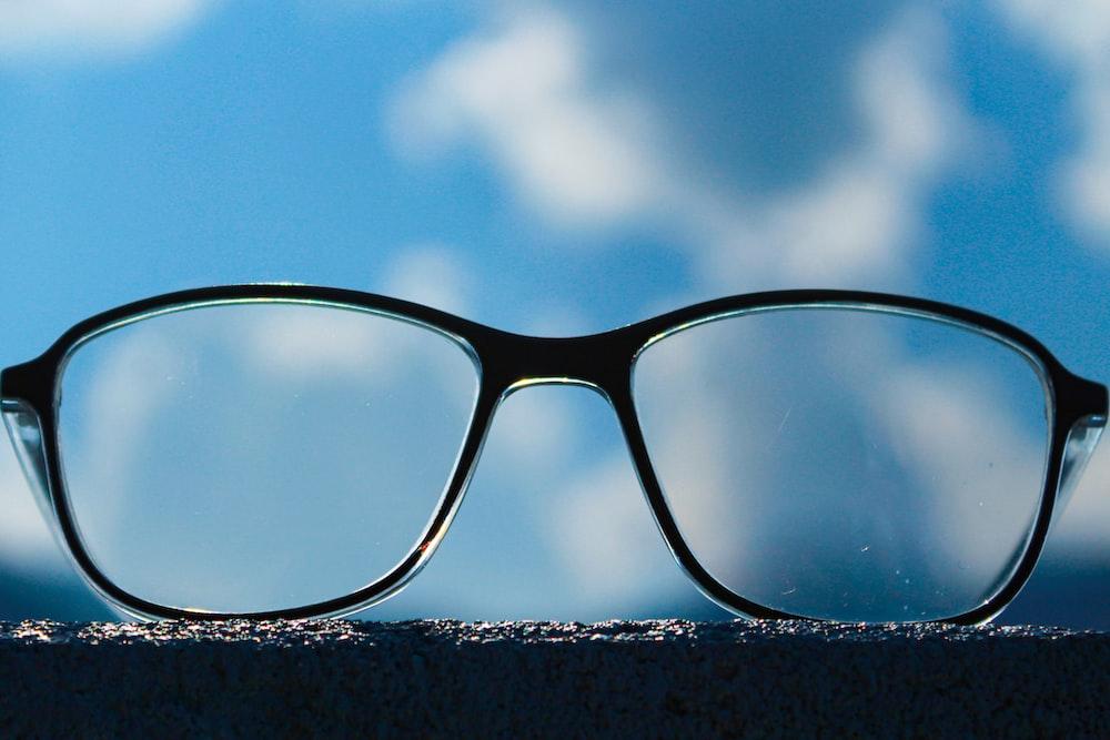 black framed eyeglasses on snow covered ground under blue sky during daytime