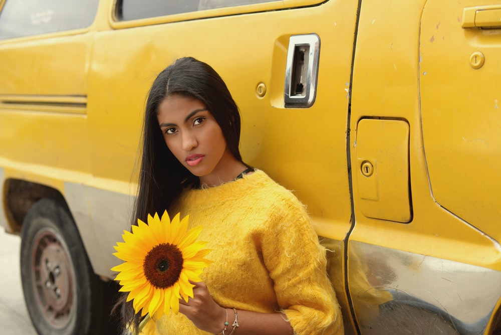woman in yellow sweater holding sunflower