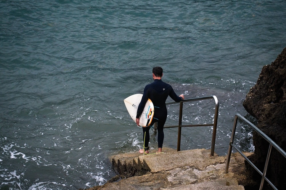 man in black shirt carrying white surfboard standing on brown rock near body of water during