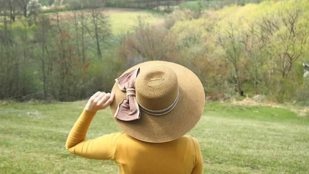woman in yellow shirt wearing brown sun hat