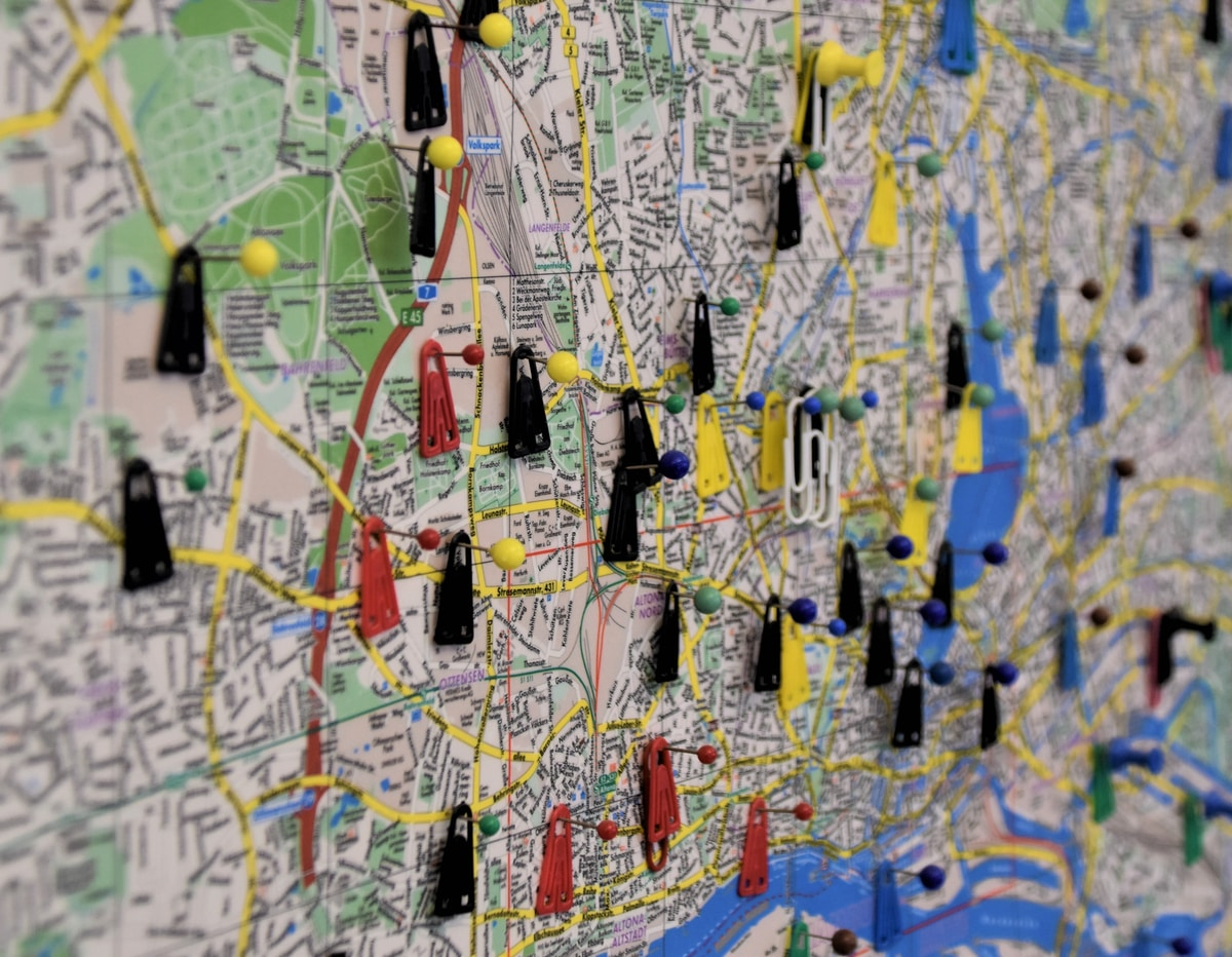 A picture of a city map with several map pins and red and black tags.