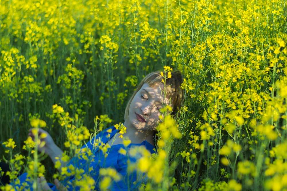 girl in blue dress on yellow flower field during daytime