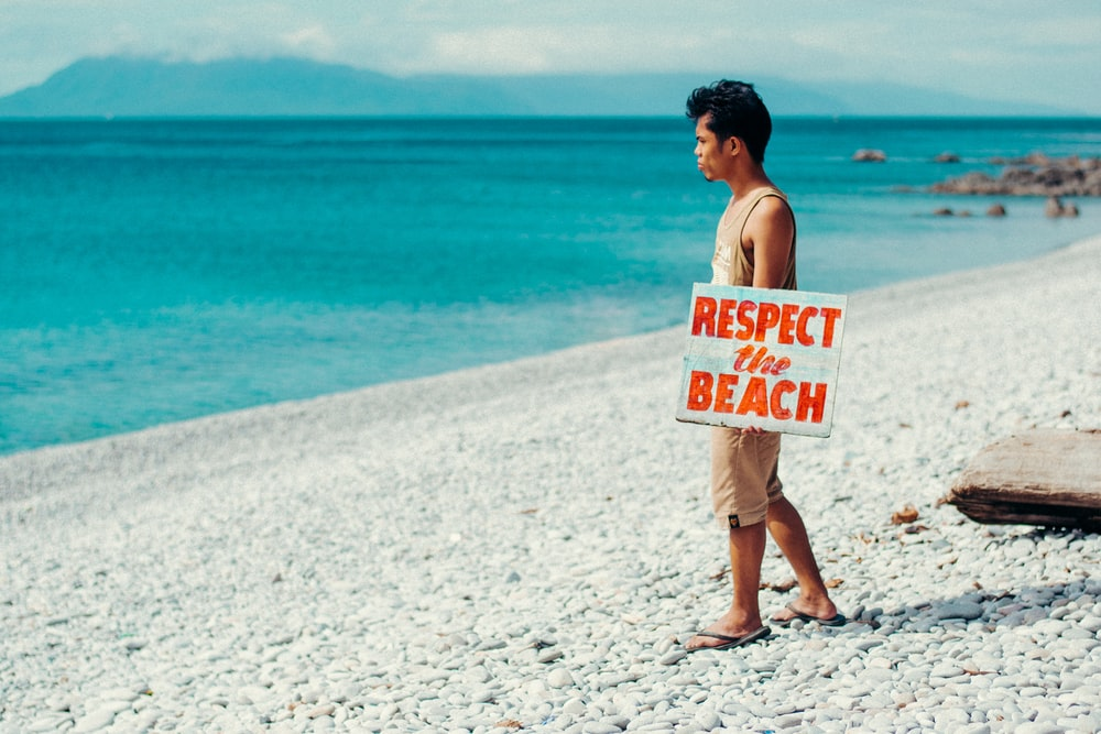 topless man holding white and red happy birthday signage standing on beach during daytime