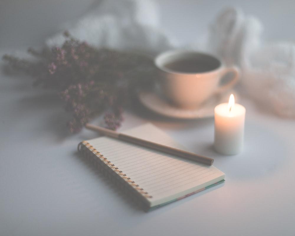 white candle on white ruled paper beside white ceramic mug