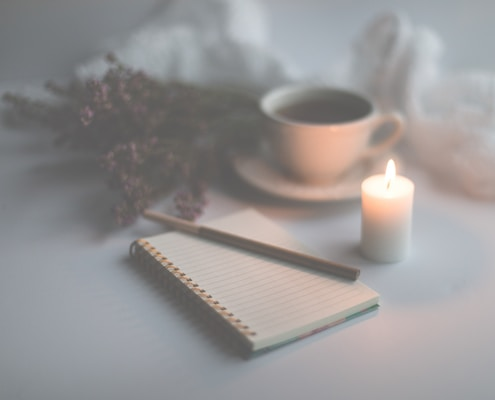 white candle on white ruled paper beside white ceramic mug