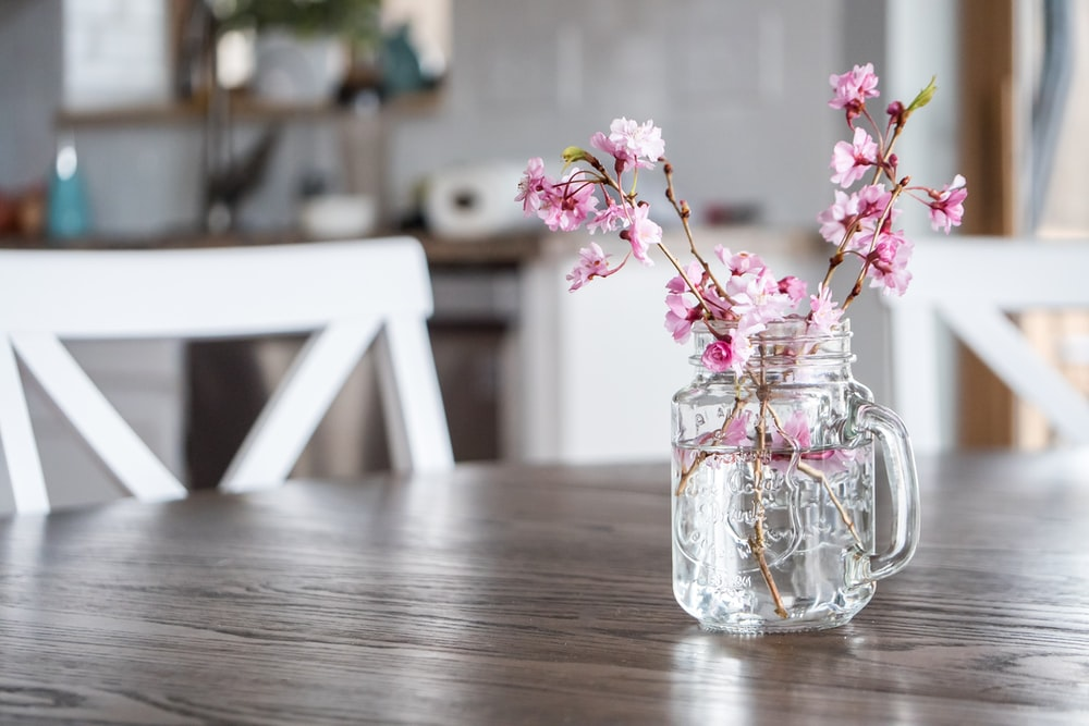 pink flowers in clear glass vase on brown wooden table