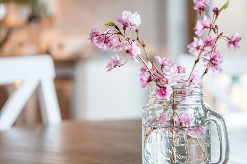 pink flowers in clear glass jar on brown wooden table