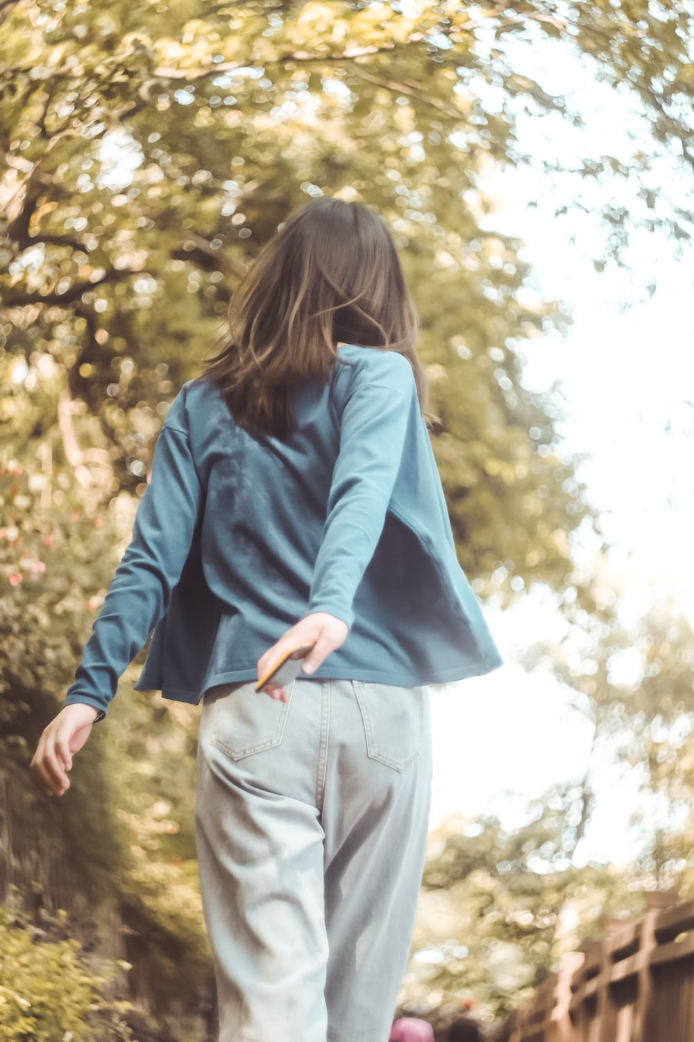 woman in blue long sleeve shirt and gray denim jeans standing on brown rock during daytime
