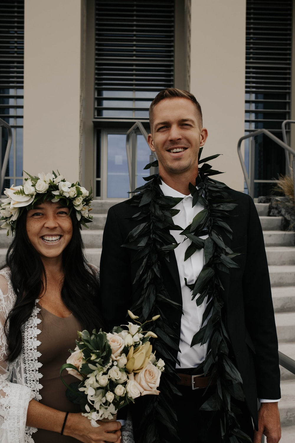 woman in white floral wedding dress beside man in black suit