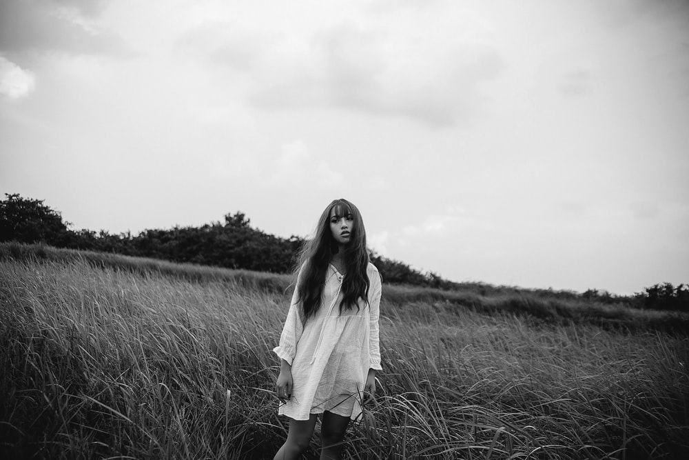 grayscale photo of woman in white dress standing on grass field