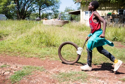 boy in red t-shirt and black pants holding brown wheel during daytime ethiopia zoom background