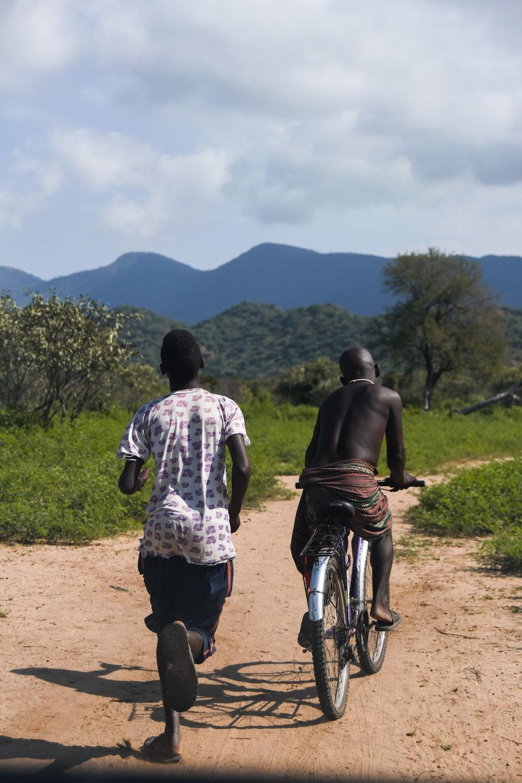 2 men walking on dirt road during daytime