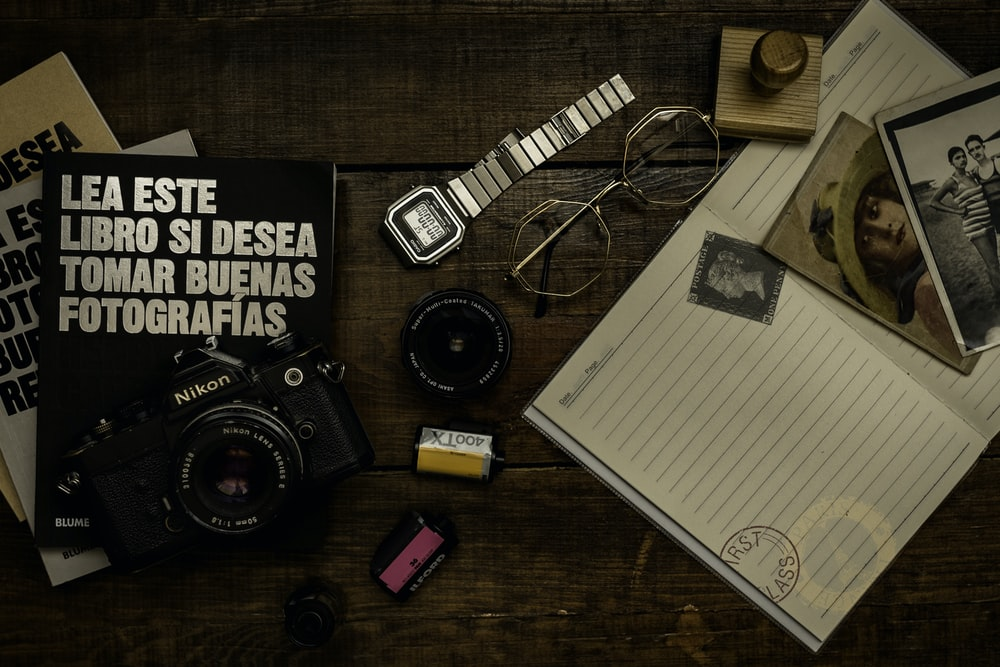 black and silver dslr camera beside white ruled paper on brown wooden table