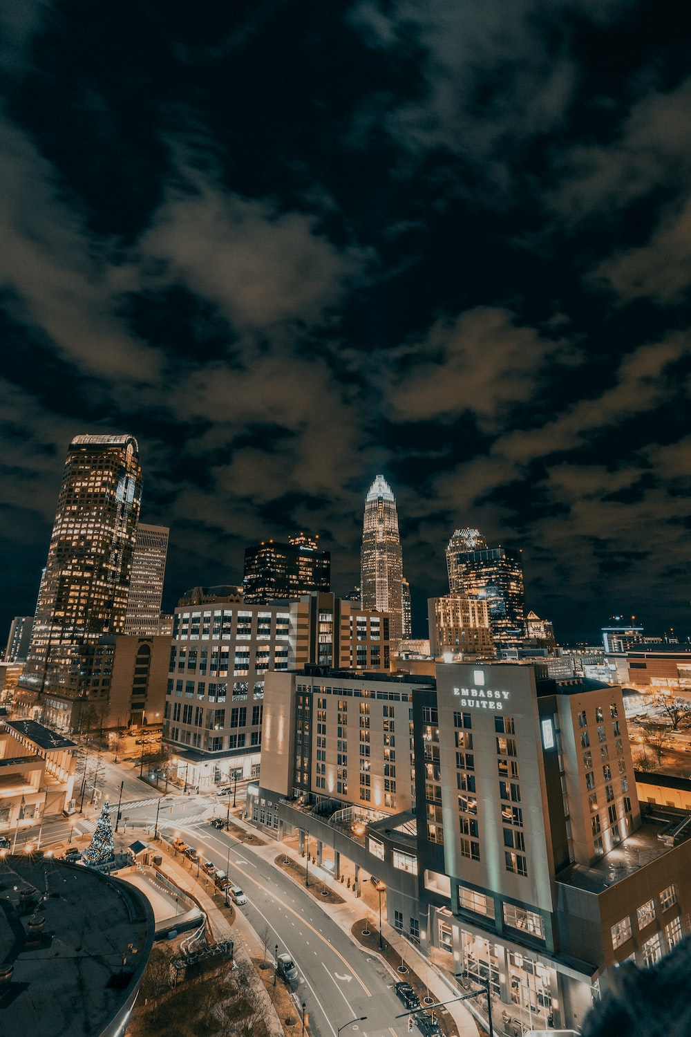city buildings under dark clouds during night time