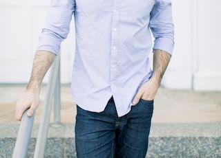 man in blue dress shirt standing near white wall