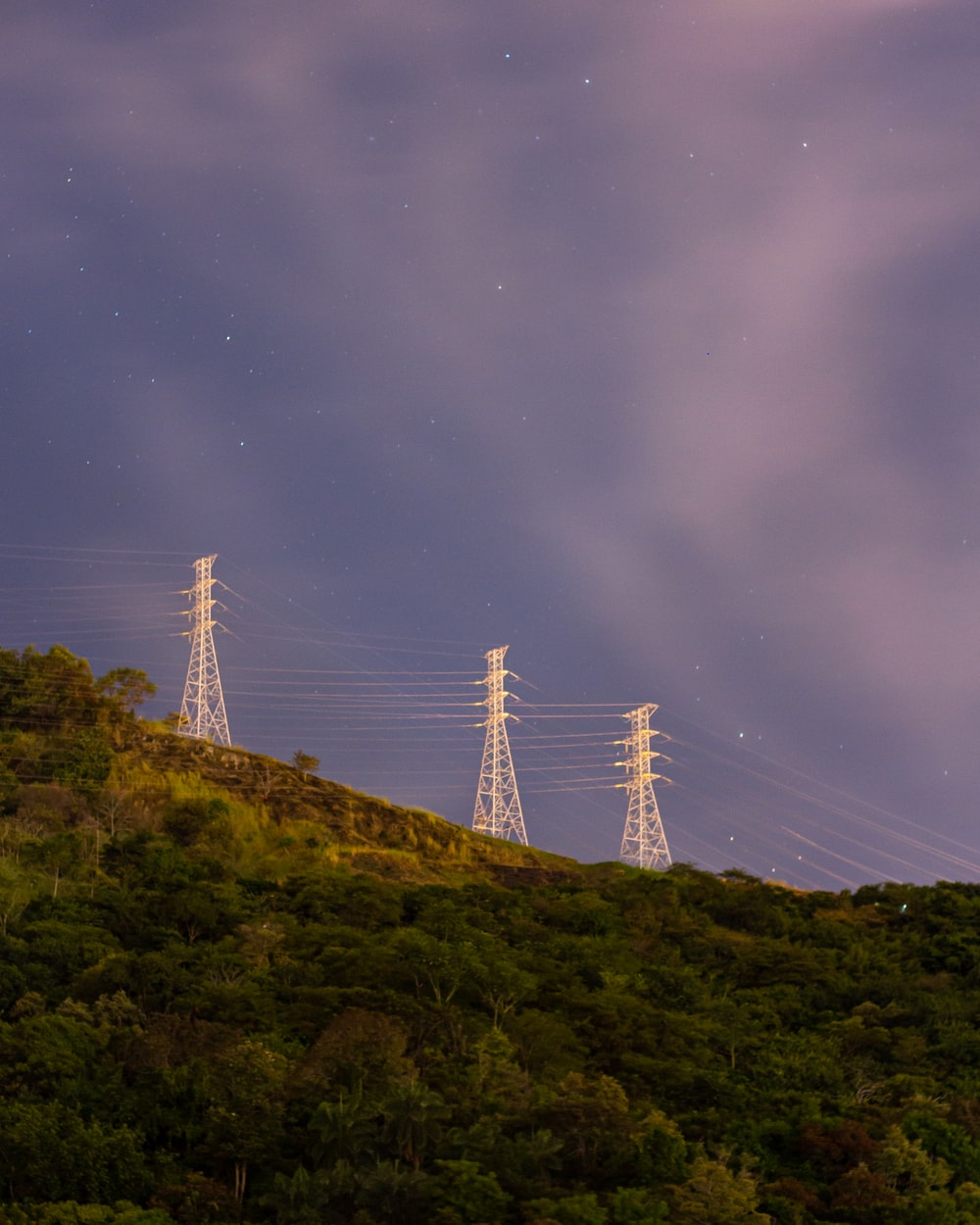 white steel bridge on top of green mountain during night time