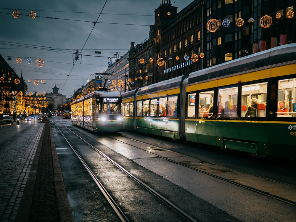 green and white tram on the street during night time