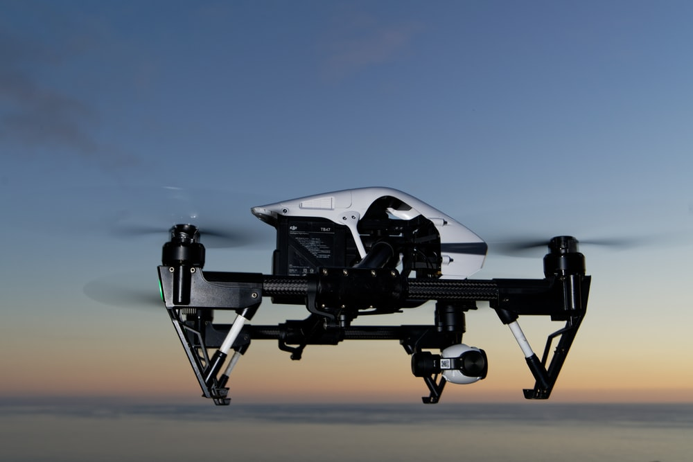 black and white drone on brown sand during daytime
