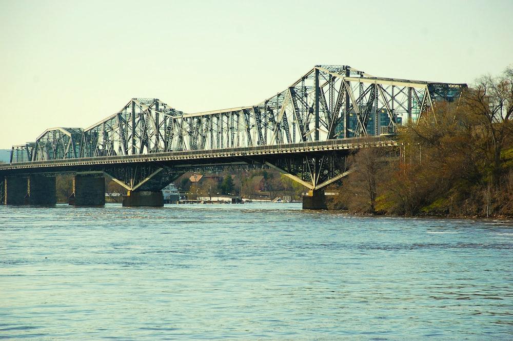 gray metal bridge over body of water during daytime