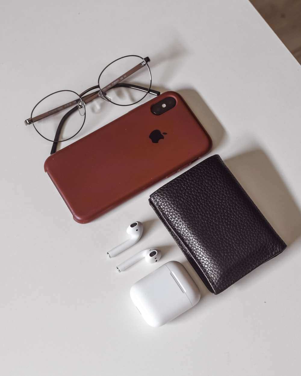 red and black iphone case beside white leather wallet